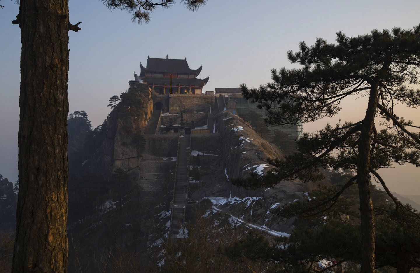 Tiantai temple reflects the golden sunlight, framed by pine trees
