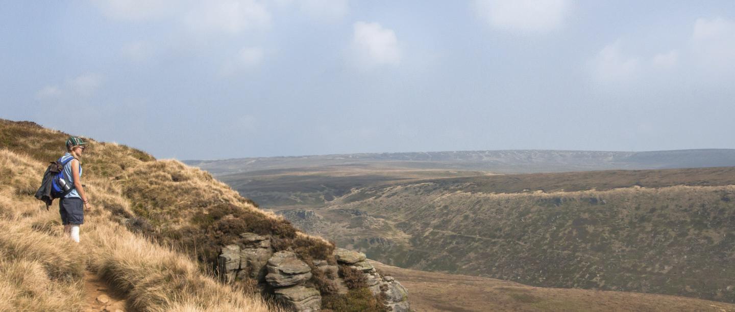 Hollie looks out on the rugged open moorland of the Peak District