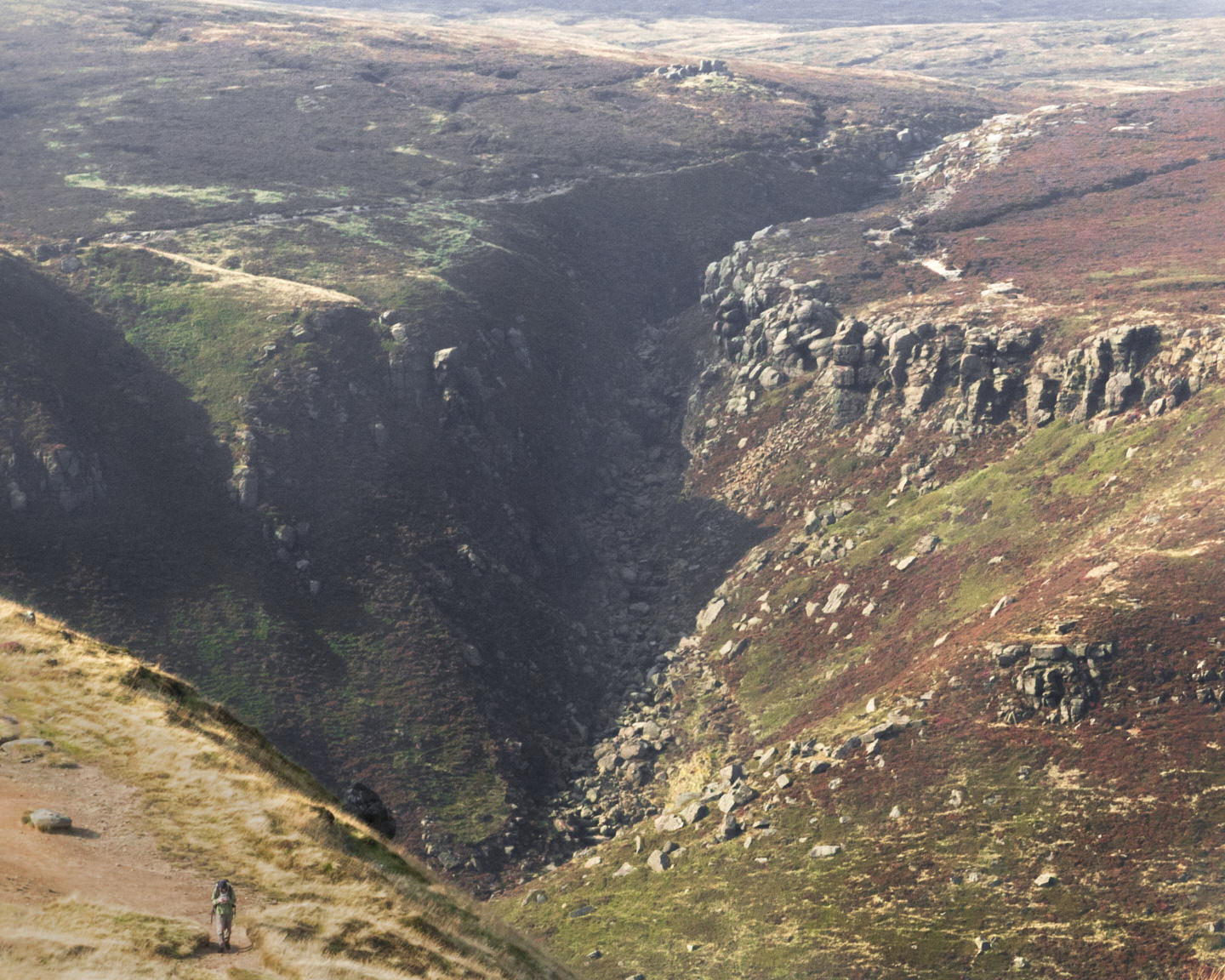 Hollie, small, walks in font of a huge cleft in the rocky Peak District hillside