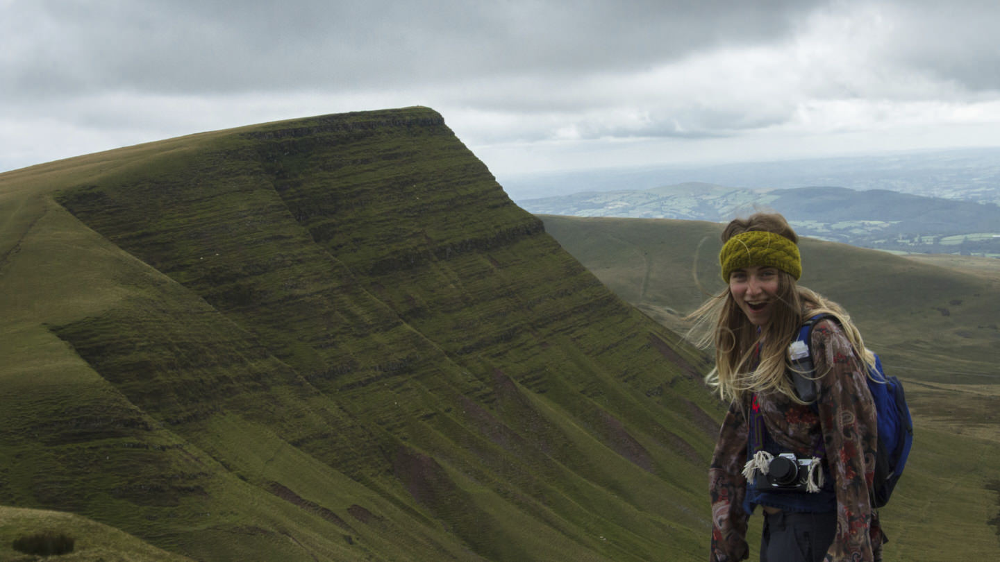 Hollie stands gasping in front of the mountain, Bannau Sir Gaer