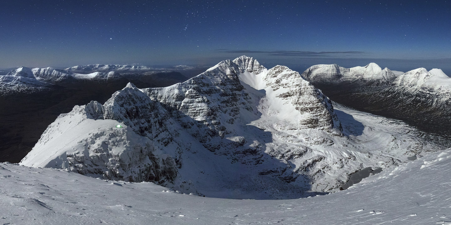 The curving, Liathach of Torridon, draped with snow, lays under a starry sky