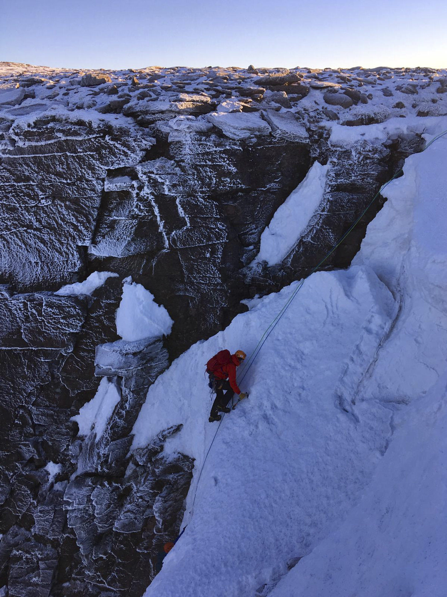 Roped up, a climber presses on up the corrie. Lifting ice axe and ready to top out into the morning sun.