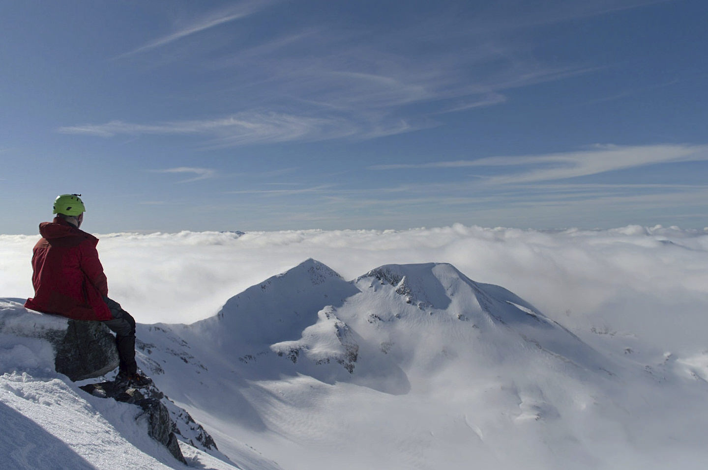 A helmeted mountaineer sits, looking out on a cloud inversion above the Mamores of Scotland