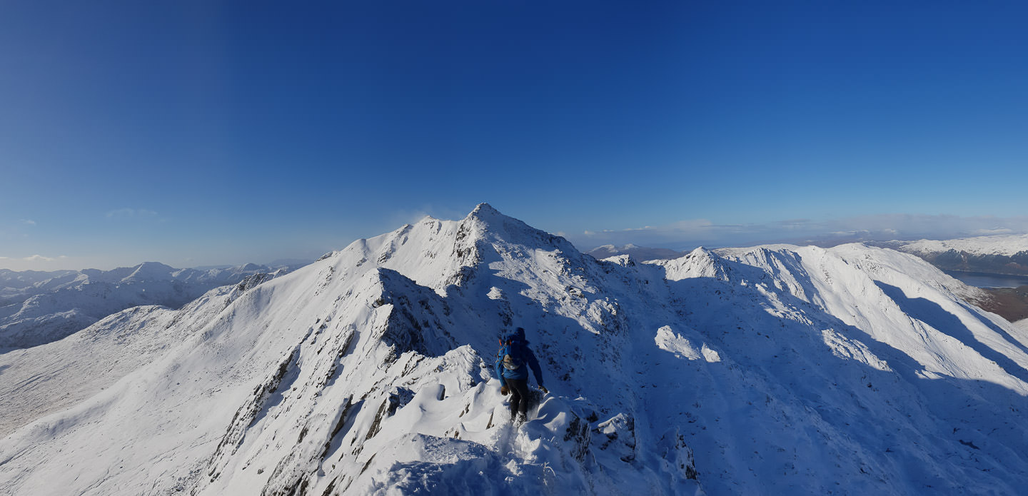 A hiker crosses a perilous ridge, banked with snow