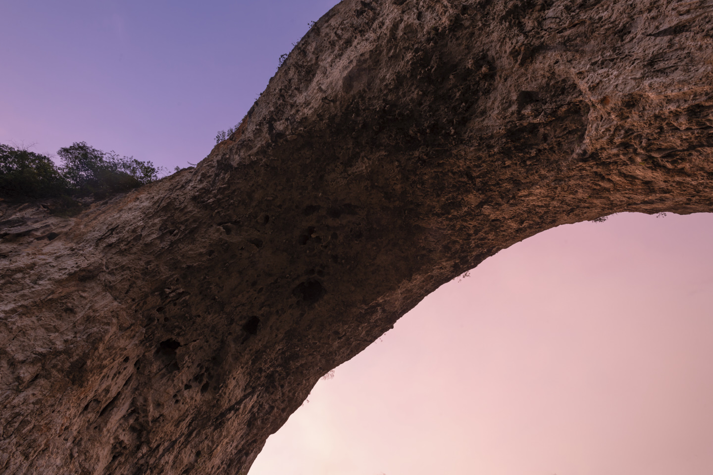 From underneath the arch, painted pink by the setting sun. Tufa hang and sky glows purple