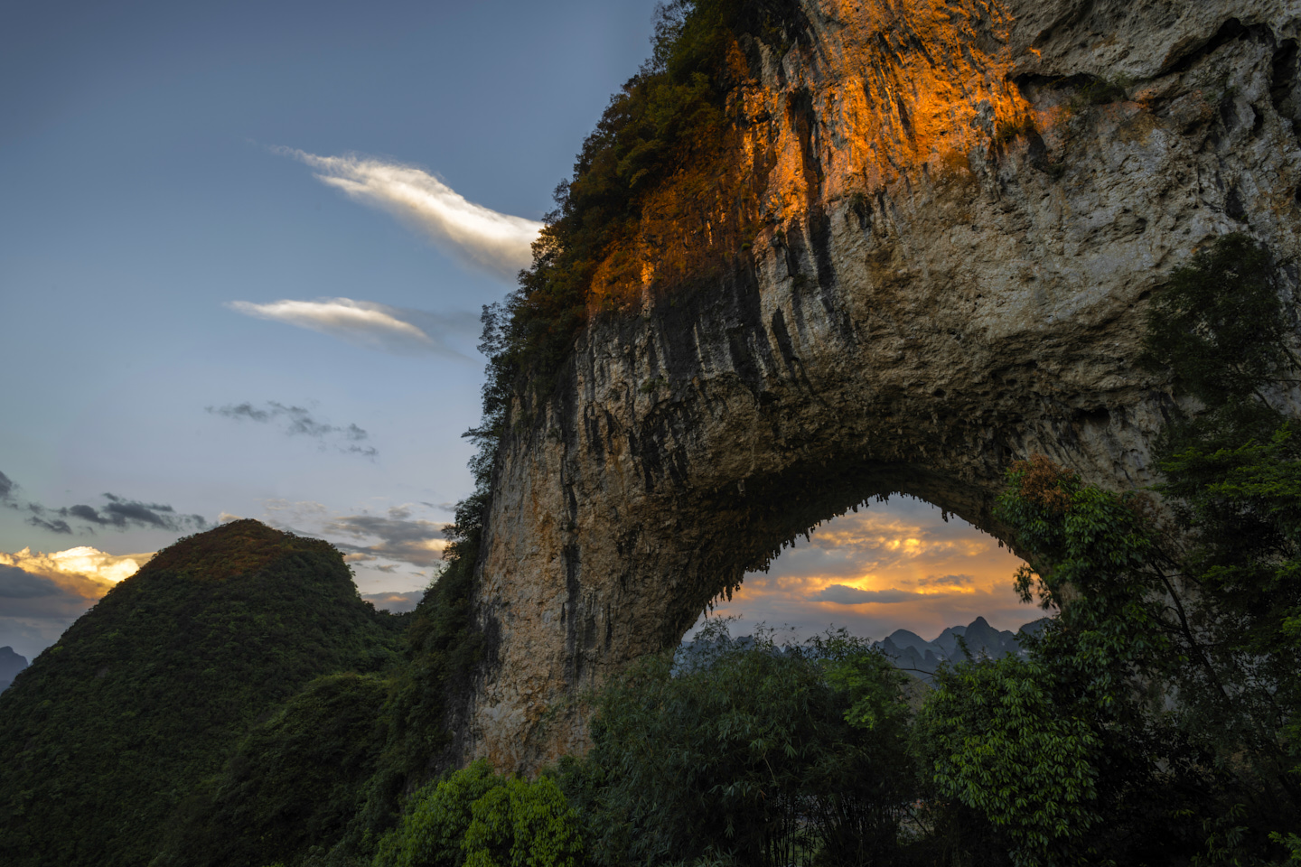 The great arch of Moon Hill is lit a fiery red as the last of the sun's rays strike its flank