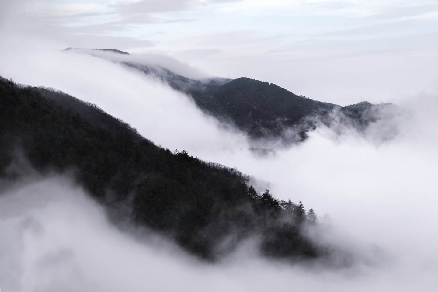 Rivers of cloud rush over mountain ridges
