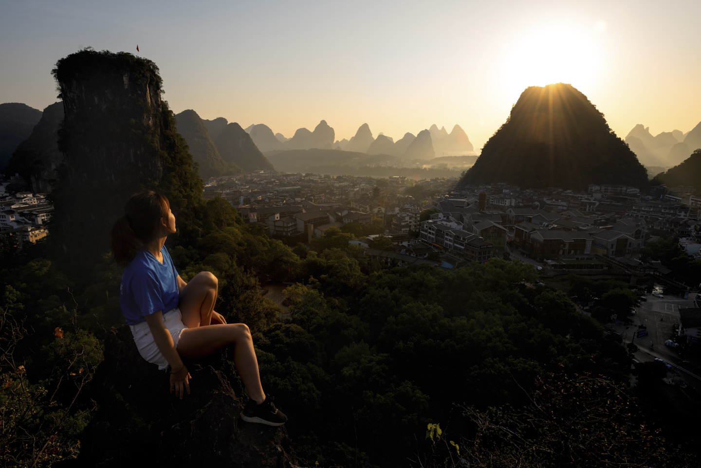 Ella sits at the summit, looking out towards Xing Ping, the Li River, distant mountains and the rising sun.