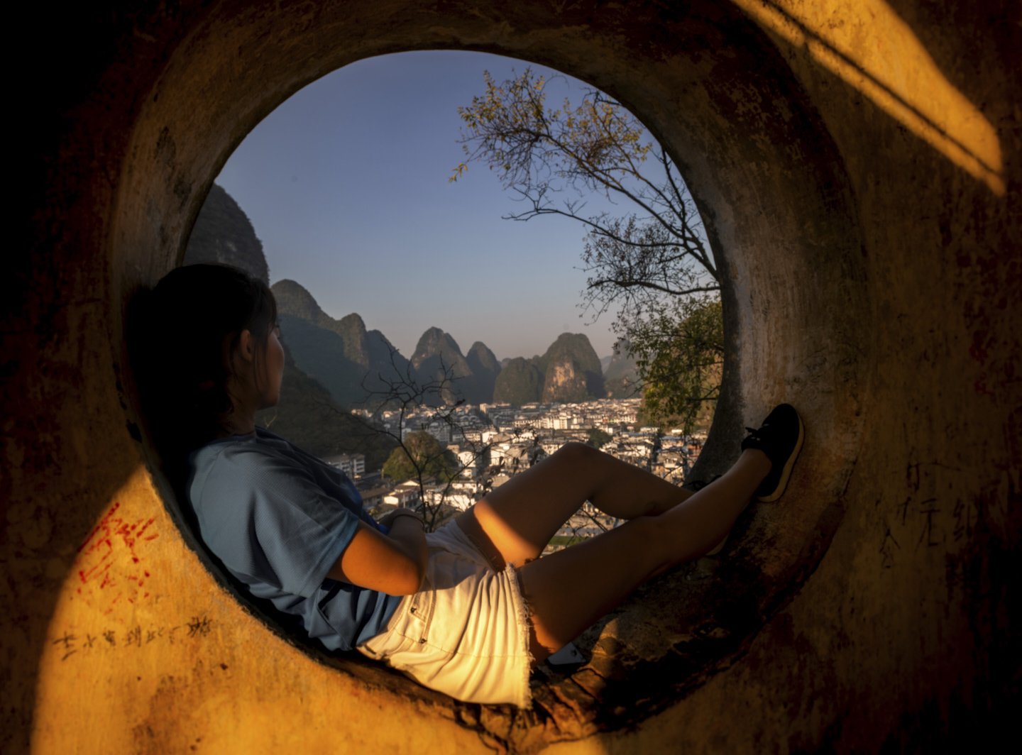 Ella sits in one of the windows at Yangshuo Park's pagoda