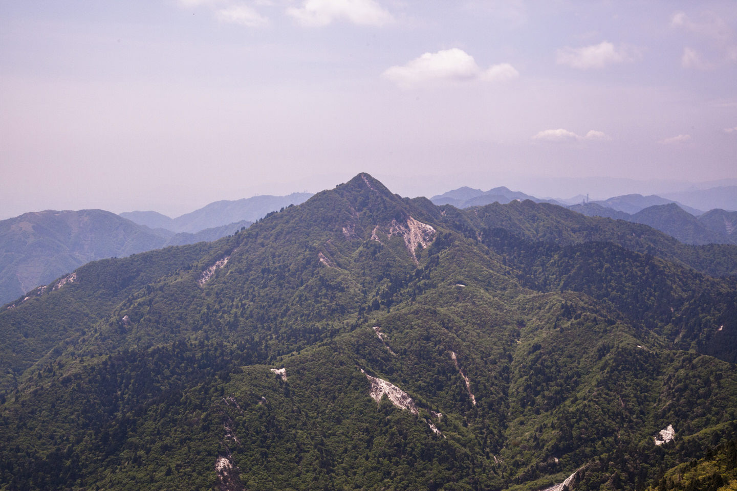 The dusty pyrimidial peak of Kamagatake rises out of thick green vegetation