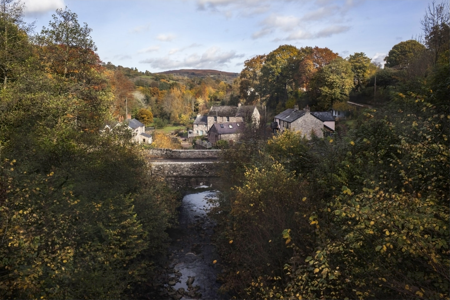 A bridge over Llangynidr and its dainty houses, ringed by autumn foliage.